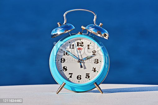 905623256 istock photo Blue alarm clock against sea background as spring forward and daylight saving concep 1211634460