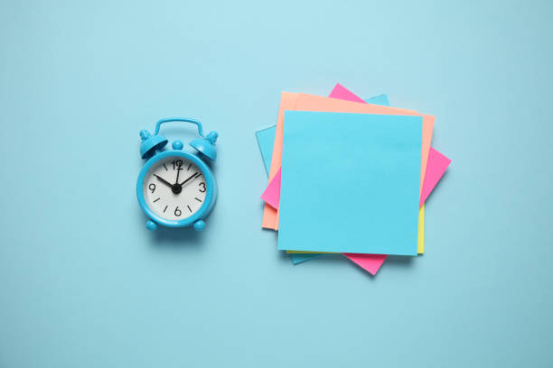 blue alarm clock and a reminder note. time management concept. copy space for text - post it foto e immagini stock