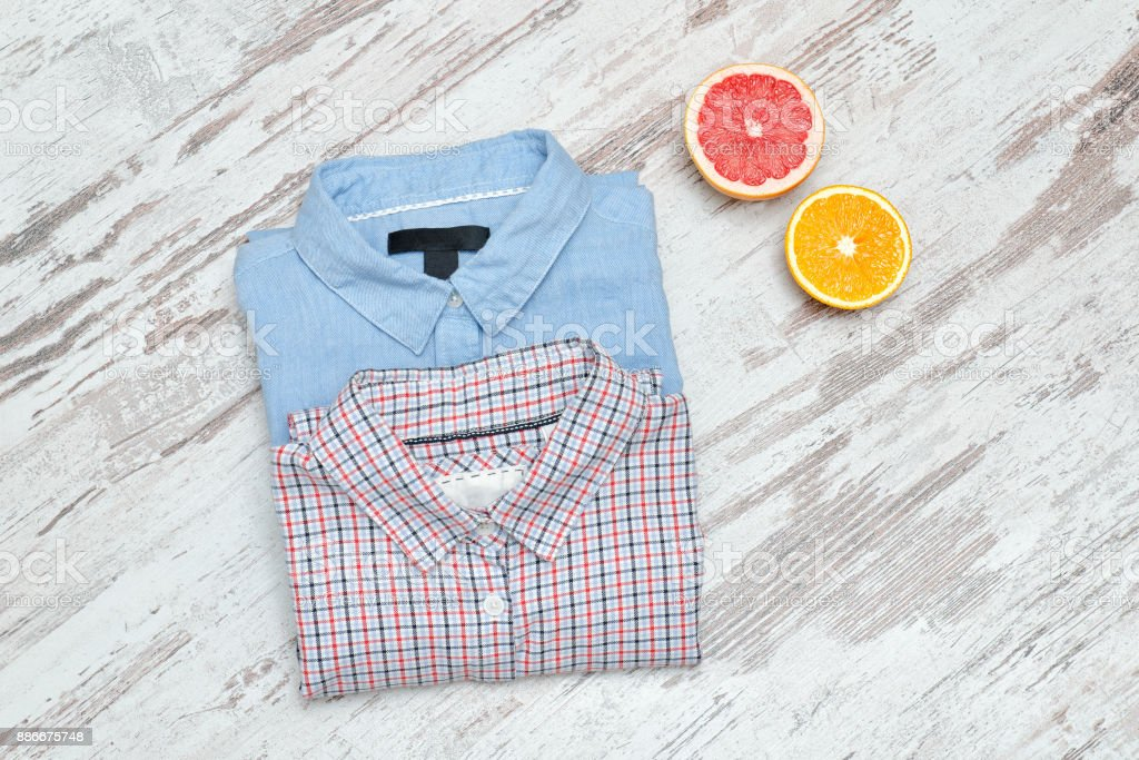 Blue an checkered shirt on a wooden background, halves of citrus. Fashionable concept stock photo