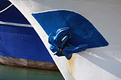 Detail shot of a blue anchor of a white fishing boat.