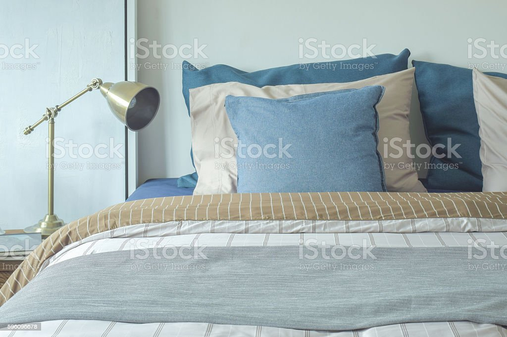 Blue and beige pillows on bed and chrome reading lamp royalty-free stock photo