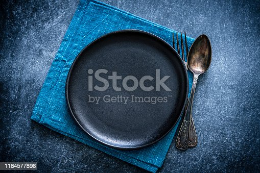 Top view of a black plate with a spoon and fork at the right side shot against a textured bluish toned background. A blue textile napkin is under the plate. Predominant colors are blue and black. Low key XXXL 42Mp studio photo taken with Sony A7rii and Sony FE 90mm f2.8 macro G OSS lens
