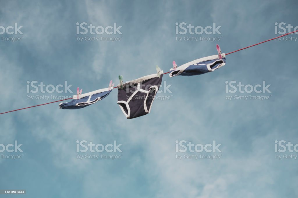 blue and black retro Y-Front underpants on a washing line against a blue sky. stock photo