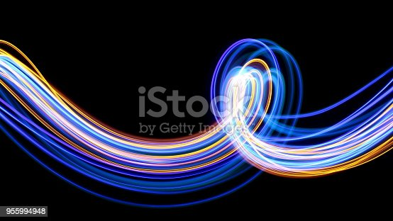 Vibrant long exposure photography of blue and metallic gold fairy lights, in swirls, loops and waves against a clean black background