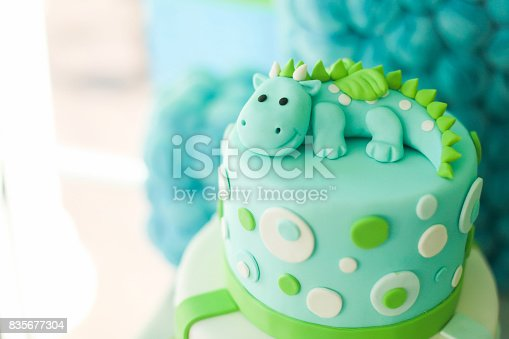 istock Blue and green birthday cake with cute dragon 835677304