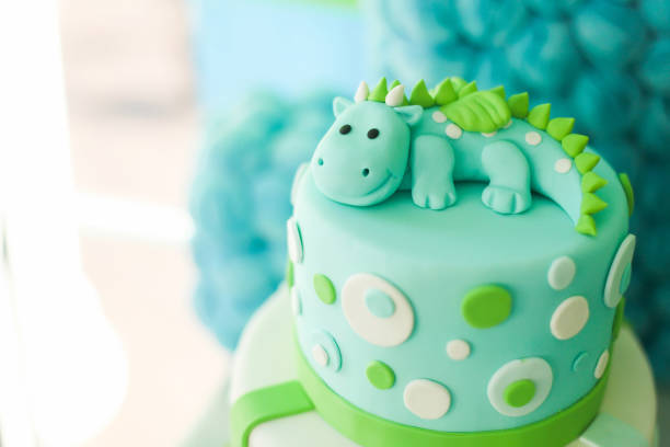 Blue and green birthday cake with cute dragon stock photo
