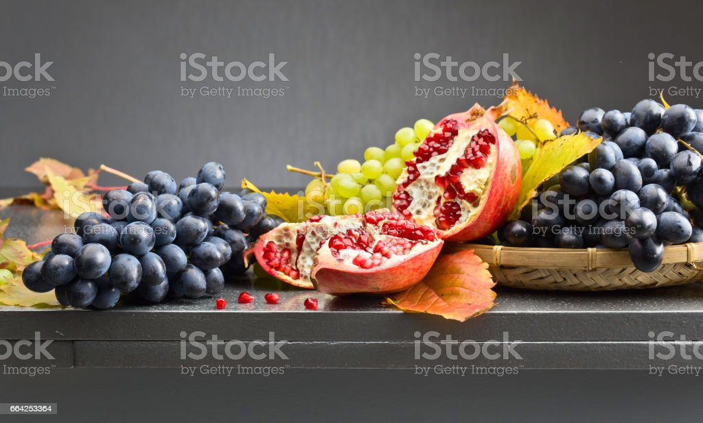 blue and green grapes with pomegranate stock photo