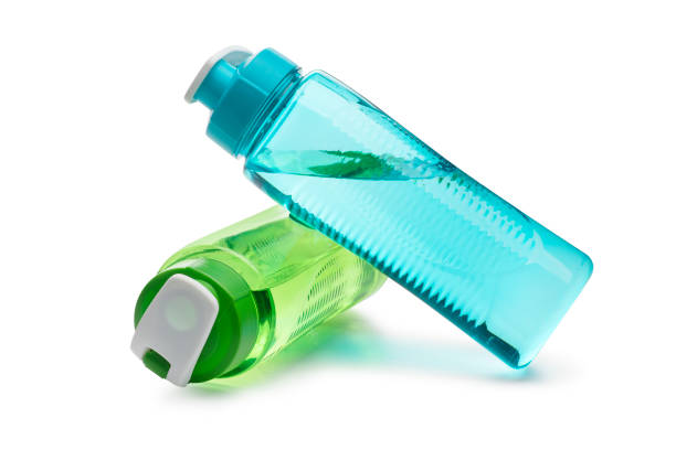 Blue and Green Water Bottle Leaning on Each other isolated on a white background stock photo