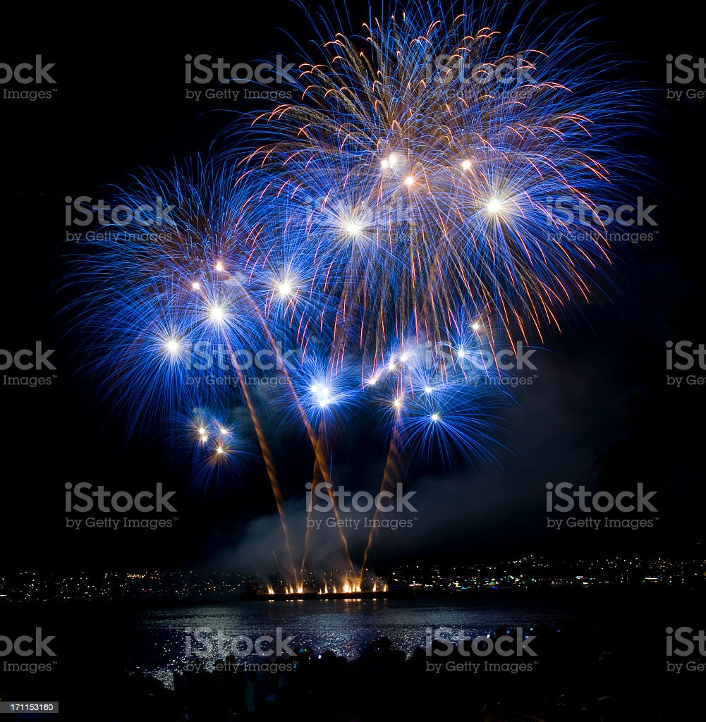 Blue and orange fireworks at night over a lake stock photo