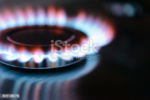 Blue and orange flames on a gas stove burner with a dark background.