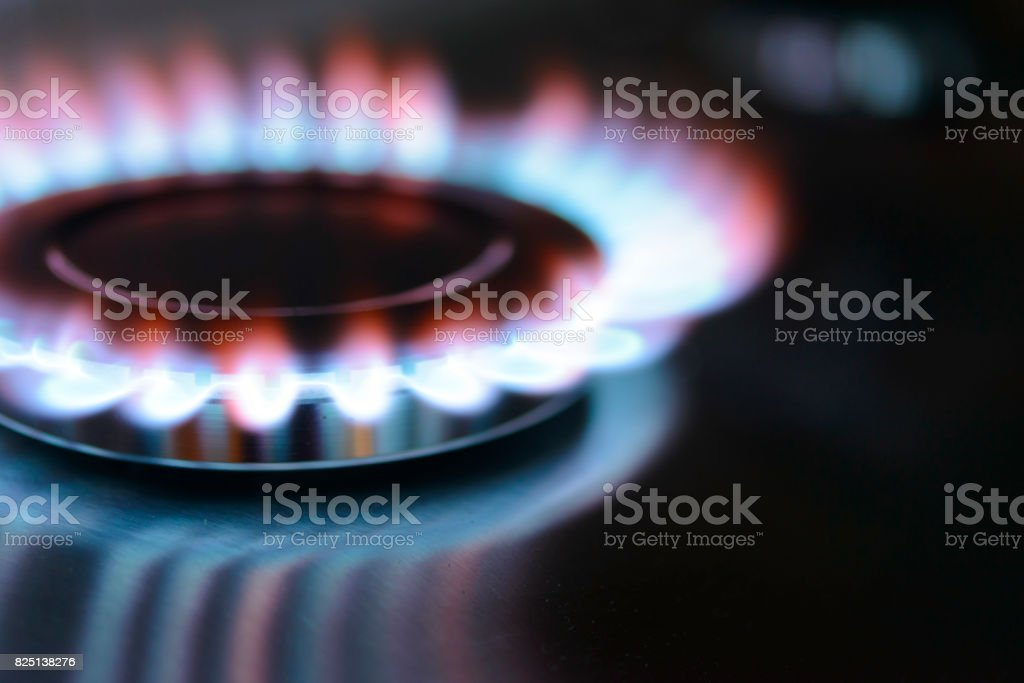 Blue and orange flames on a gas stove burner stock photo