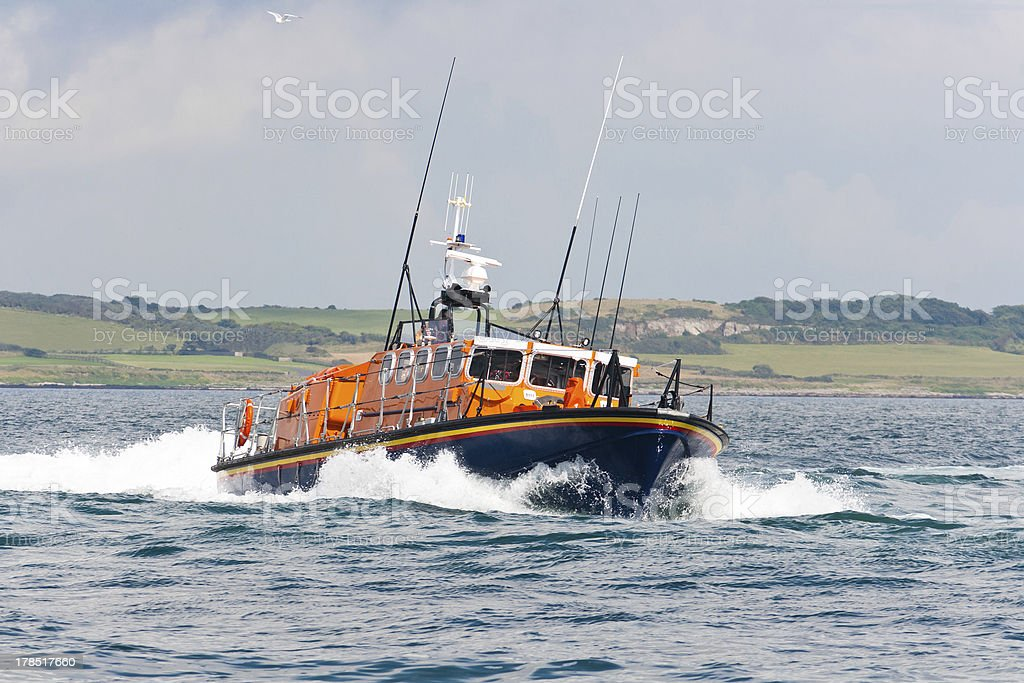 Blue and orange lifeboat in action at sea. stock photo