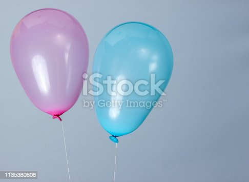 945748362istockphoto Blue and pink balloons on a gray background 1135380608