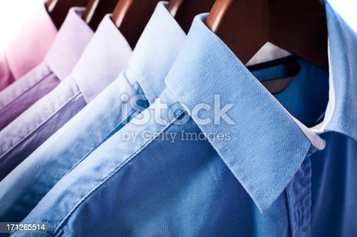 Close-up of blue and pink elegant button down shirts are hanging on wooden hangers.