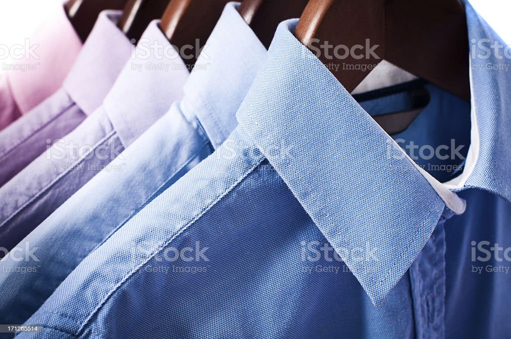 Blue and pink elegant button down shirts hanging on hangers stock photo