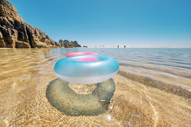 blue and pink rubber rings floating on the clear shallow idyllic sea at pedn vounder beach on a perfect sunny june day. - rubber ring stock pictures, royalty-free photos & images
