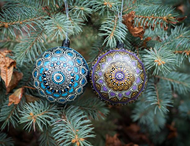 Blue and purple christmas balls hanging on pine tree stock photo