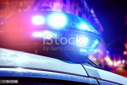 istock Blue and red light flasher of a patrol police car at night. Police force department in full activity with turned on lights. Night patrolling of the city with emergency flashers. Security sirens on the police vehicle. 1179413769