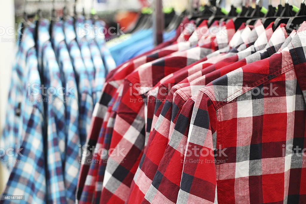 blue and red men shirts on hanger stock photo