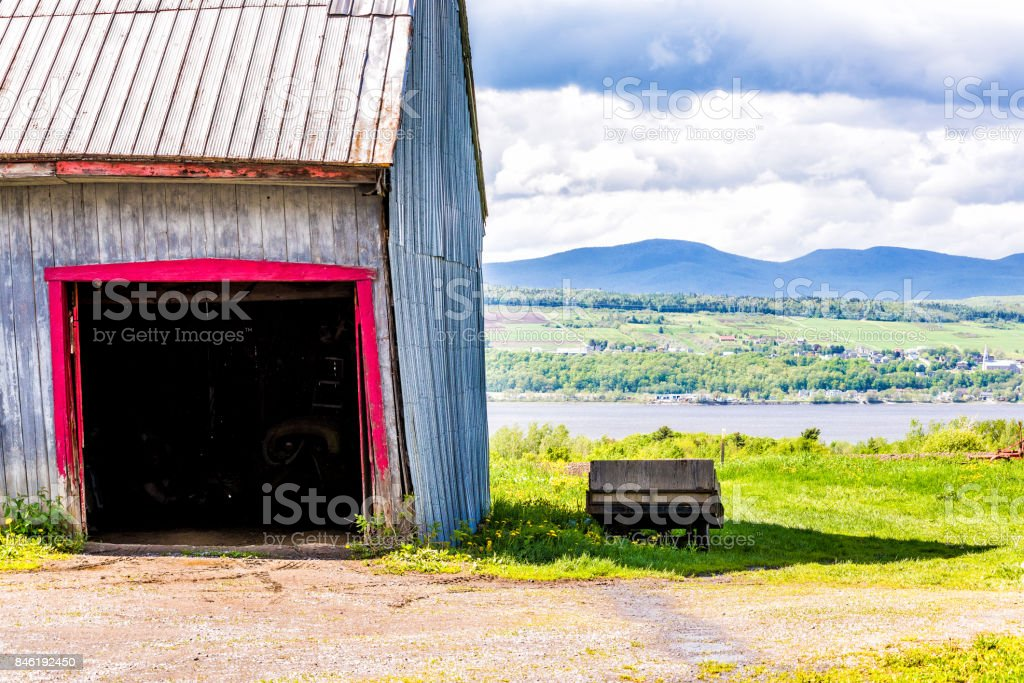 Blue and red painted old vintage shed or barn with wooden wagon overlooking river in summer landscape field in countryside stock photo