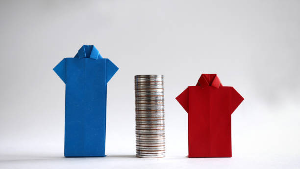 Blue and red shirts made of paper with piles of coins in between. The concept of gender employment and wage gap in the enterprise. Blue and red shirts made of paper with piles of coins in between. The concept of gender employment and wage gap in the enterprise. discriminatory stock pictures, royalty-free photos & images