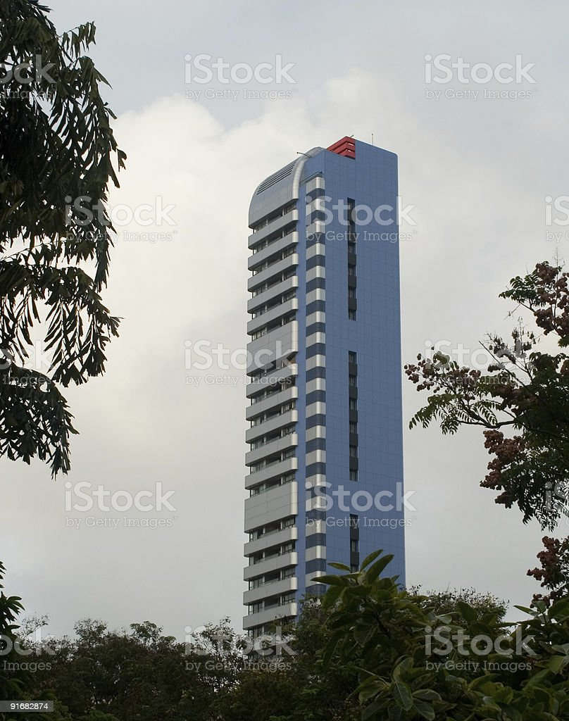 Blue and silver building amidst trees, Mumbai, India royalty-free stock photo