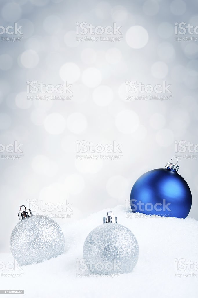 Blue and silver Christmas baubles on snow, silver background stock photo