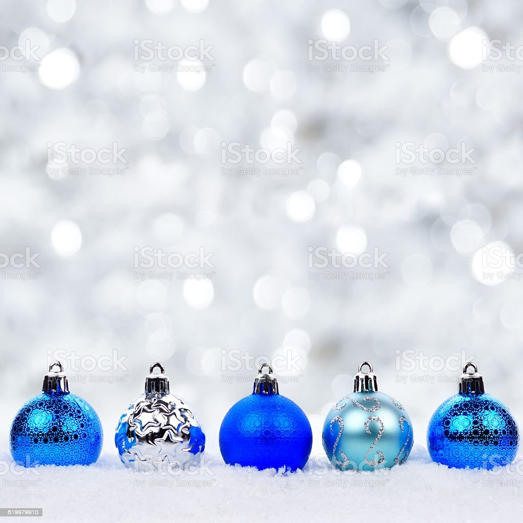 Blue and silver Christmas ornaments in snow with twinkling background stock photo
