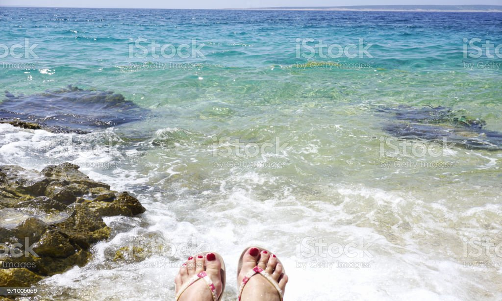 Blue and turquoise seacoast and women toes in the water on the beach stock photo