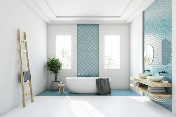 Blue and white bathroom, white tub White and blue bathroom interior with a round white tub, two narrow windows, a tree in a pot and a ladder in a corner. Side view. 3d rendering mock up bathtub stock pictures, royalty-free photos & images