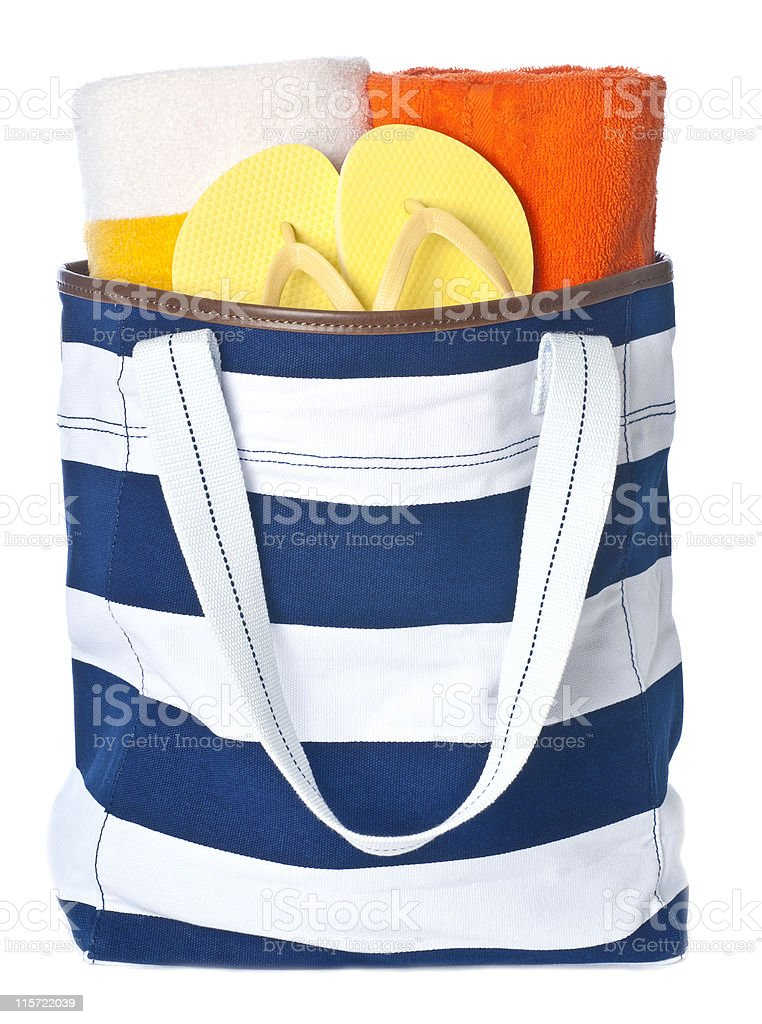 Blue and white beach bag with towels and sandals inside stock photo