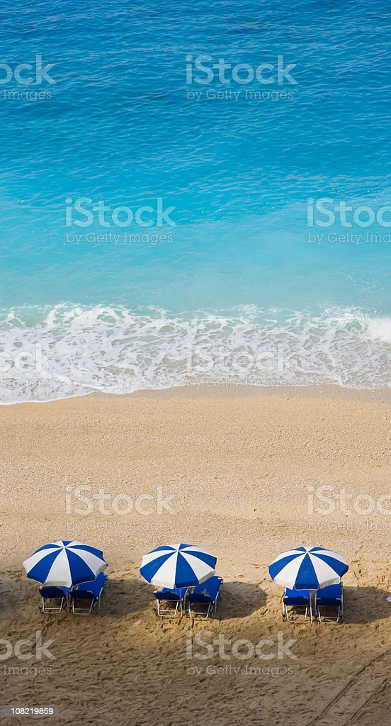 Blue and White Beach Umbrellas on Sand by Water royalty-free stock photo