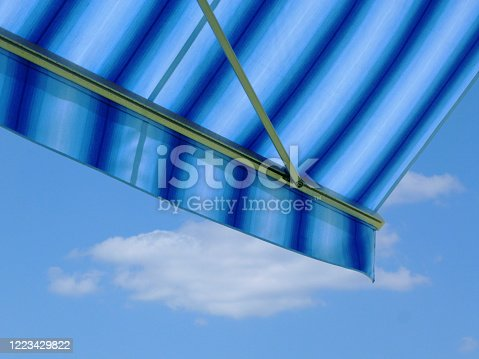 blue and white canvas fabric awning detail. blue sky and white clouds. sunny summer day. sun protection concept. UV exposure. bright striped light blue  waterproof and UV protective material.