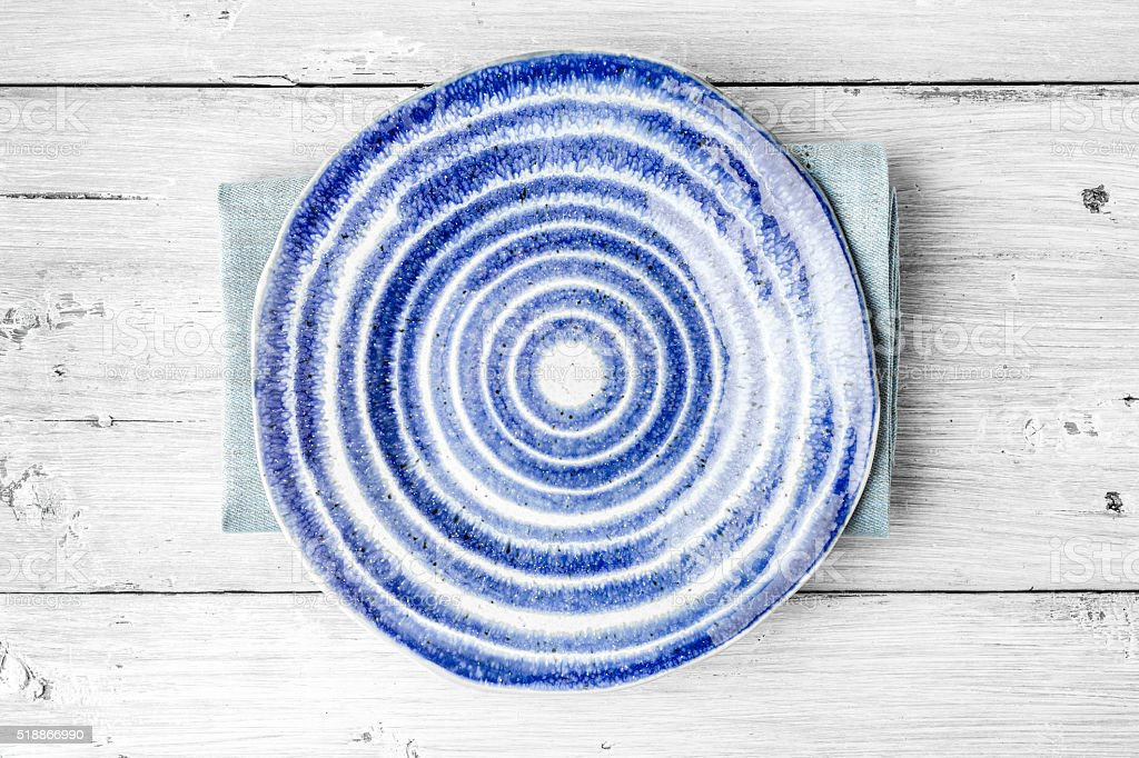 Blue and white ceramic plate on the white wooden table stock photo