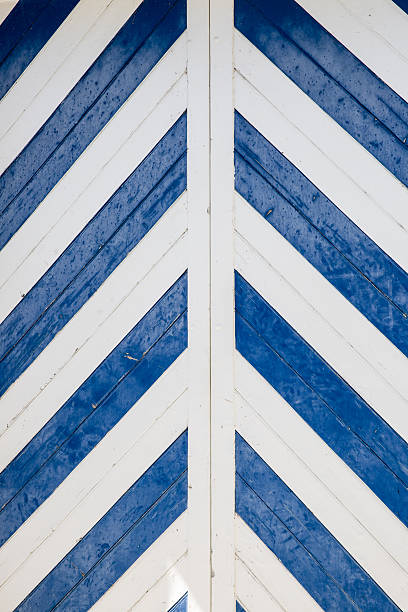 blue and white chevron pattern on a wooden door - chevron stock photos and pictures
