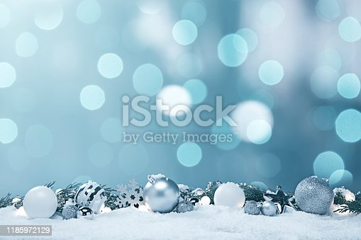 This is a photograph of blue and white and Silver Christmas ornaments shot in the snow surrounded by glowing Christmas lights surrouned by evergreen palm tree branches. There are no people in the photograph