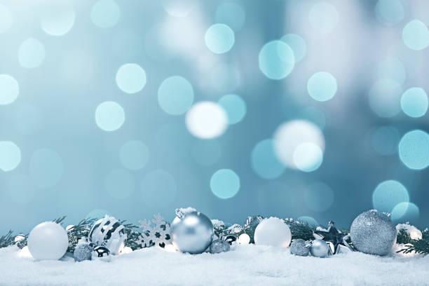 파란색과 흰색 크리스마스 장식품과 소나무 가지와 눈의 조명 - holiday 뉴스 사진 이미지