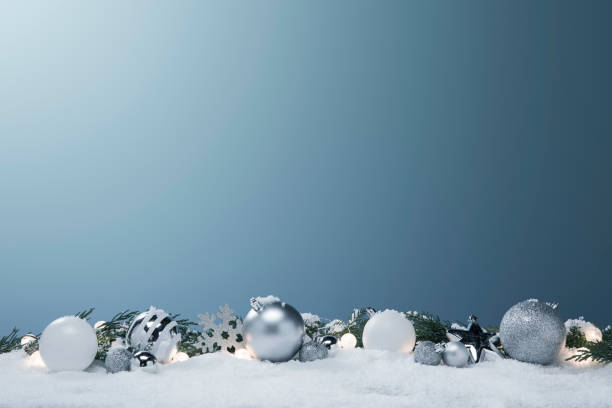 Blue and white Christmas ornaments and Lights in the snow with pine tree branches stock photo