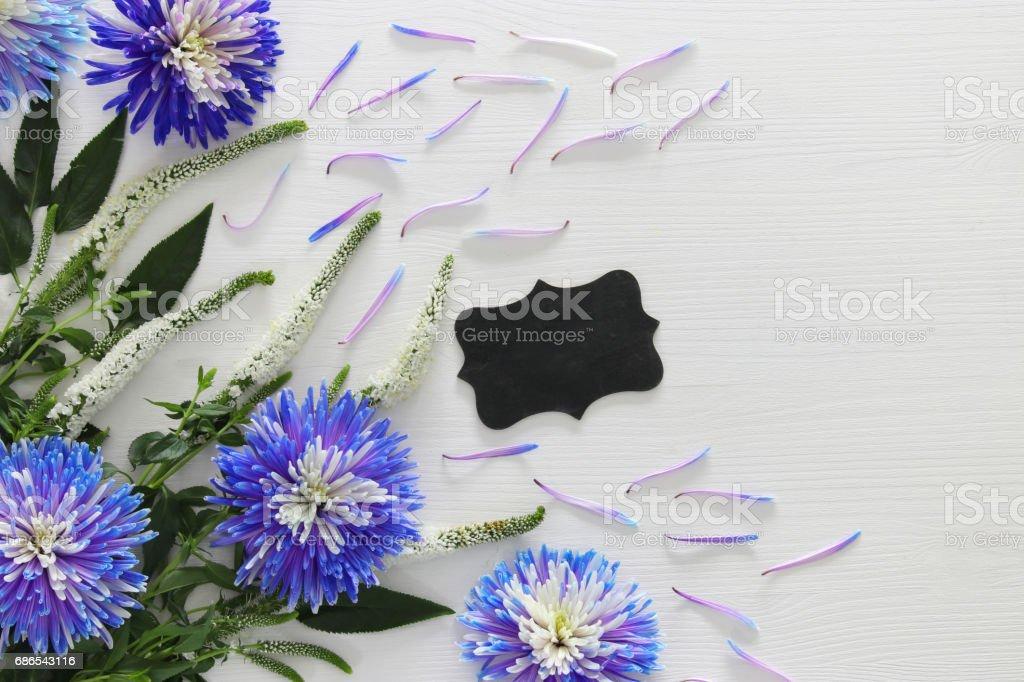 Tableau noir et arrangement de fleurs blanches et bleues photo libre de droits