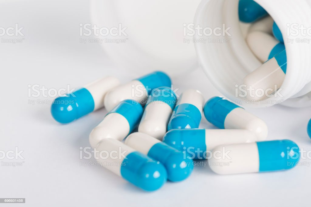 Blue and white pill capsules and bottle on white background stock photo