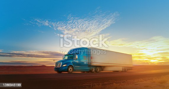Blue and white semi-truck speeding on a single lane road USA