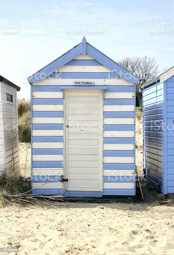 Blue and white striped beach hut stock photo