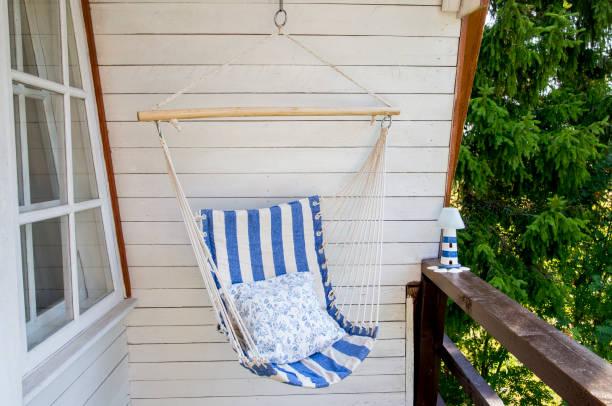 blauw en wit gestreepte patroon string en katoen hangmat opknoping stoel, wit geschilderde houten bord achtergrond. ontspannen op het platteland home tuin balkon buiten op zomerse dag concept. - schommelen bungelen stockfoto's en -beelden