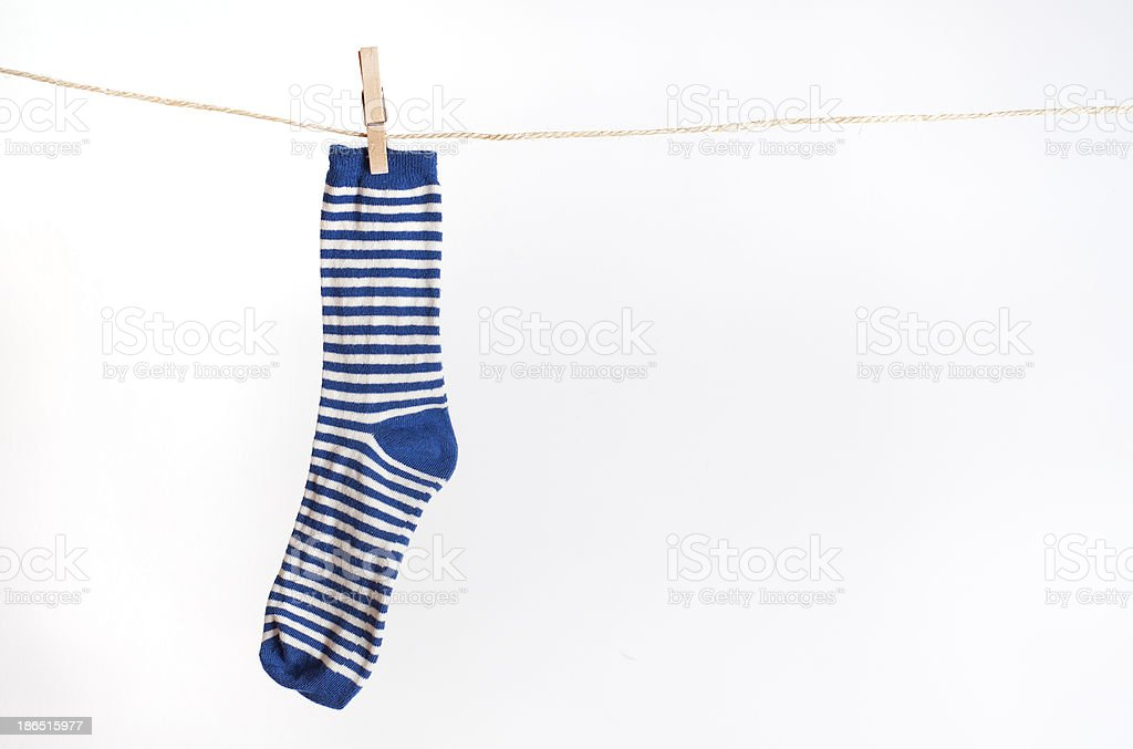 Blue and white striped sock hanging from a rope royalty-free stock photo