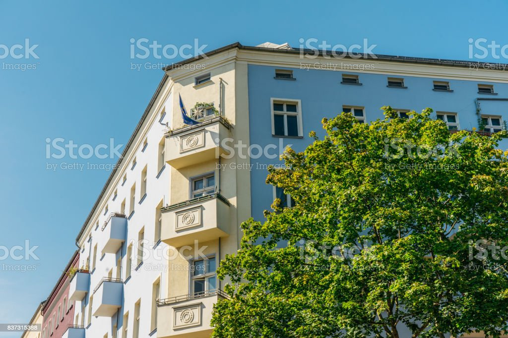 blue and yellow corner house on a summer day stock photo