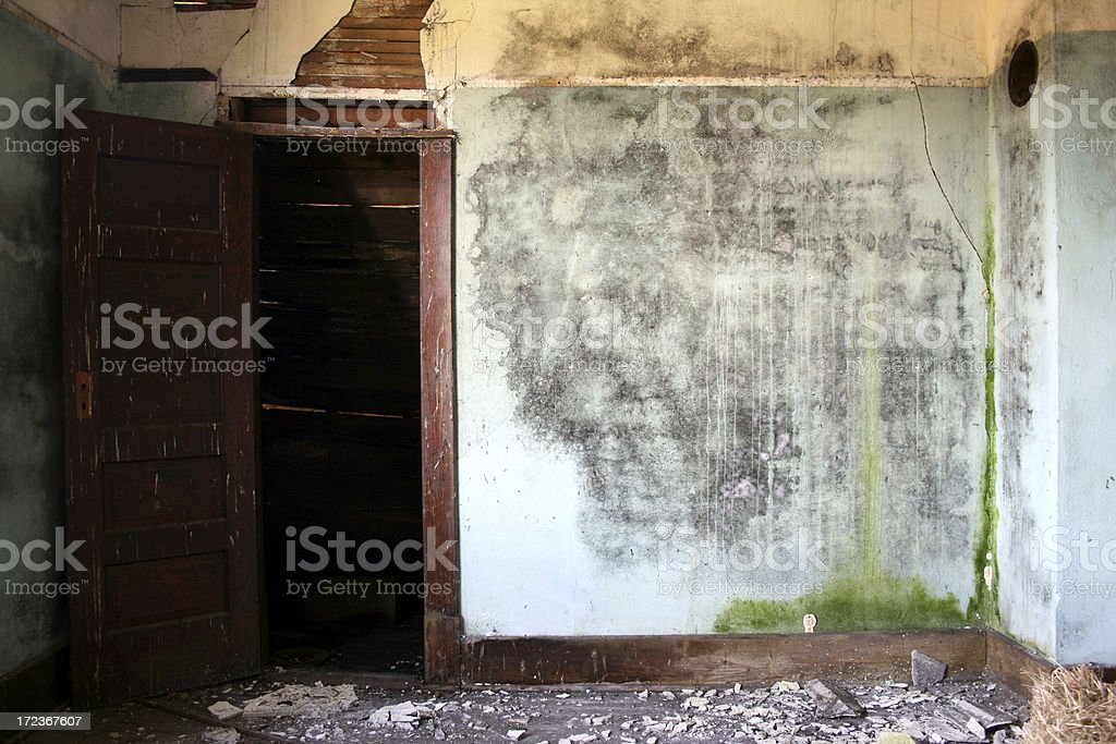 Blue and yellow crumbling water damaged plaster walls with doorway royalty-free stock photo