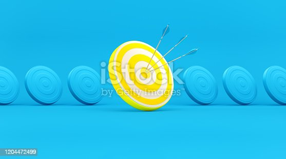 istock Blue and Yellow Dart Targets in a Row over Blue Background 1204472499