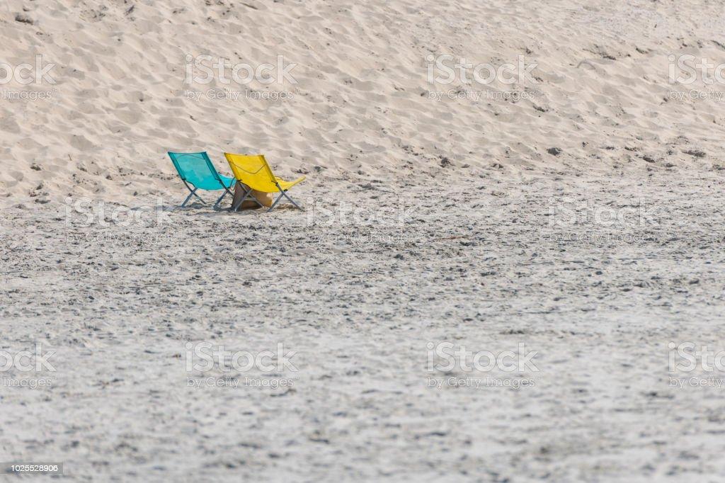 Ein blau und gelb Klappstuhl am Nordseestrand – Foto