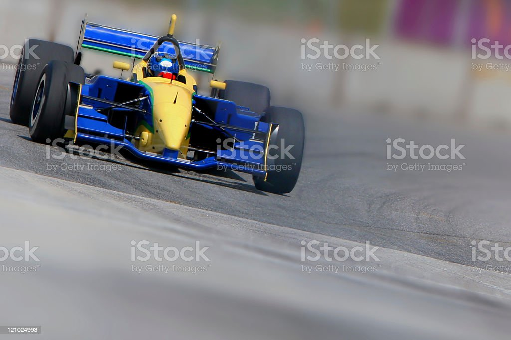 Blue and yellow racecar in motion on a racetrack stock photo