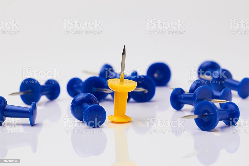 Blue and yellow thumbtacks on a white background. stock photo
